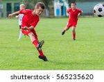 boy kicking soccer ball on... | Shutterstock . vector #565235620