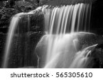 Waterfall in forest landscape long exposure flowing through trees and over rocks in black and white - stock photo