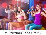 friends holding dumbbells while ... | Shutterstock . vector #565419040
