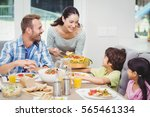 smiling mother serving food to... | Shutterstock . vector #565461334