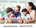 happy family using digital... | Shutterstock . vector #565477474