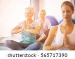 instructor performing yoga with ... | Shutterstock . vector #565717390