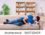 man watching football at home... | Shutterstock . vector #565720429
