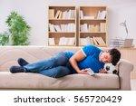 man watching football at home... | Shutterstock . vector #565720429