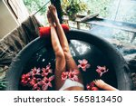 Small photo of Woman relaxing in round outdoor bath with tropical flowers. Organic skin care in kawa hot bath in luxury spa resort.