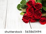 Stock photo red roses on a old wooden table 565865494