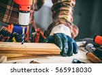 Gloved carpenter working with an electric drill on a wooden plank - stock photo