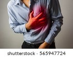 man having heart ache   holding ... | Shutterstock . vector #565947724