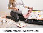 woman packing baby clothes for... | Shutterstock . vector #565996228