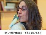 woman feeding green budgerigar | Shutterstock . vector #566157664