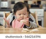 asian baby girl eating bread... | Shutterstock . vector #566216596