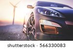 Stock photo the image in front of the sports car scene behind as the sun going down with wind turbines in the 566330083