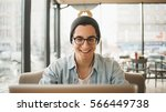 Handsome businessman in casual wear and eyeglasses is using a laptop. Guy in light blue jeans jacket with hat having pleasant conversation with friend. He is smiling and looking at screen