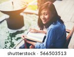 woman reading book on park bench | Shutterstock . vector #566503513