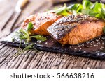 Stock photo grilled salmon fillets sesame seeds herb decoration and black slate board on old oak table 566638216