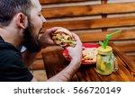 young man eating a cheeseburger.... | Shutterstock . vector #566720149