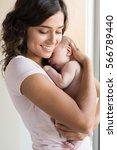 pretty woman holding a newborn... | Shutterstock . vector #566789440