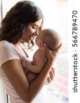 pretty woman holding a newborn... | Shutterstock . vector #566789470
