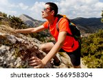young guy climbing on rock | Shutterstock . vector #566958304