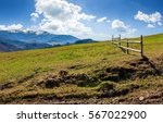 wooden fence on grassy hillside near mountains with snowy peaks in spring - stock photo