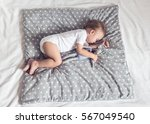 sleeping baby in bed holding a... | Shutterstock . vector #567049540