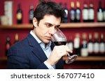 sommelier tasting red wine | Shutterstock . vector #567077410