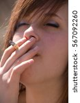 Small photo of Cute young woman enjoys a quiet moment outside as she smokes a fag, eyes closed. Brunette girl with blue eye shadow.