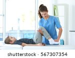 physiotherapist working with... | Shutterstock . vector #567307354