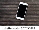 white smartphone on dark wooden ... | Shutterstock . vector #567358324