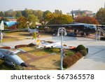 Small photo of SEOUL - NOV 4, 2015: Freight big airplane near small and trees in military museum. South Korea started aerodynamic testing of next-generation fighter