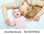 mother kisses baby lying on the ...   Shutterstock . vector #567659503