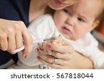 mother cutting fingernails of... | Shutterstock . vector #567818044