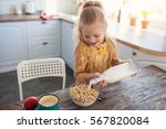 cute little girl eating cereal... | Shutterstock . vector #567820084