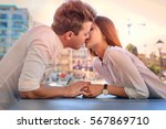 Small photo of Lovely teenagers kissing by the table