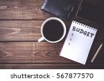 Small photo of Budget planing concept. Top view of notepad with word Budget, mobile phone, cup of coffee, pouch on wooden background. Write idea success solution concept. Vintage toned picture. Copy space