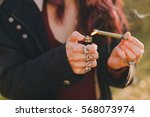 Small photo of girl lighting up a blunt in the woods