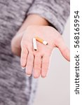 Small photo of Closeup of broken cigarette on male hand. Winning with addicted nicotine problems, stop smoking. Quitting from addiction concept.