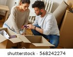 young couple unpacking... | Shutterstock . vector #568242274