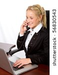 a businesswoman working on a computer and talking on a telephone - stock photo