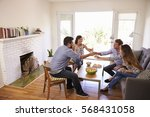 couple entertaining friends at... | Shutterstock . vector #568431058