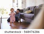 parents watching baby daughter... | Shutterstock . vector #568476286