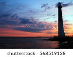 Stock photo the tall tower of barnegat light contrasts with the multi colored sky of sunrise 568519138