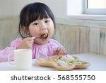 asian little girl having lunch | Shutterstock . vector #568555750