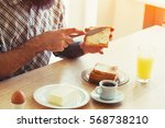 male hands spreading butter on... | Shutterstock . vector #568738210