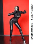 Small photo of Pretty Zentai Catsuit Theatre Actress Acting Girl Posing In Latex Rubber PVC Vinyl Carbon Clothes High Fashion Vogue Style Red Background Isolated