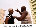 Small photo of Substance abuse, crime, social issues, drugs and narcotics. Hispanic and black gang members meeting and fighting over drug dose. Man threatening to kill pusher.