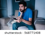 bored man watching tv on the... | Shutterstock . vector #568771408
