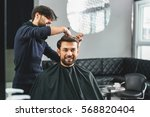 happy guy getting haircut by...   Shutterstock . vector #568820404