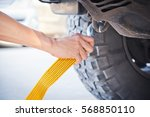 hand holding yellow car towing... | Shutterstock . vector #568850110