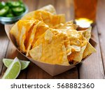 nachos and cheese with lime... | Shutterstock . vector #568882360